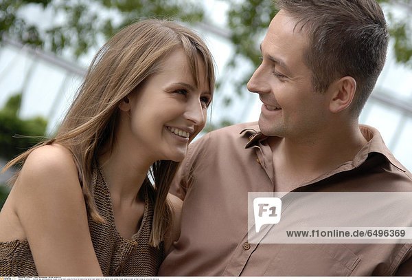 1243753 outdoor day summer people couple woman man young 20-25 girl brunette long haired dark haired 30-35 mature smile smiling blouse beige blouses portrait close up horizontal embrace