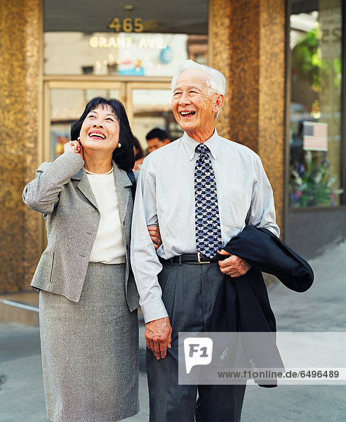 Senior couple laughing and walking in urban setting