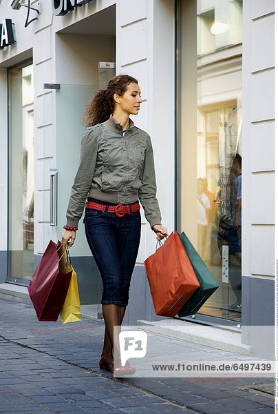 1245122 outdoor day summer city street people woman young 25-30 brunette long haired smile smiling bag shopping close up relax rest shop shops jacket green trousers jean jeans vertical belt red