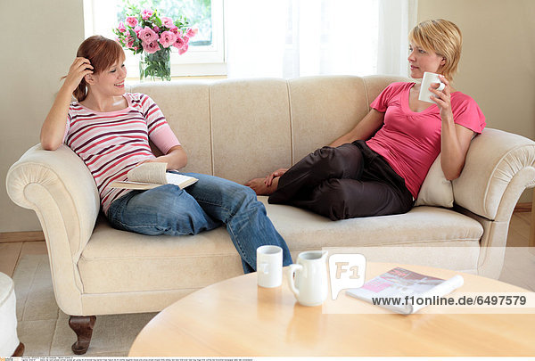 1244747 indoor flat room people woman women girl young 20-25 blonde long haired fringe mature 40-45 mother daughter blouse pink stripe stripes striped smile smiling rest relax hold book read mug mugs drink coffee tea horizontal newspaper table talk conversation