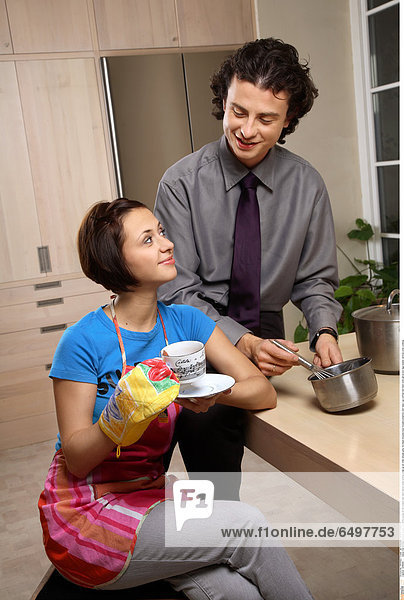 1248656 indoor flat kitchen people woman brunette young 25-30 couple man dark haired smile smiling close up sit chair blouse grey tie black blouses blue trousers pinafore rest relax cup coffee tea feed oven glove pot egg beater vertical cook cooking