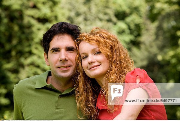 1247256 outdoor day summer park people woman young girl 20-25 blonde long haired smile smiling blouse red couple man 25-30 dark haired blouses green rest relax horizontal close up portrait