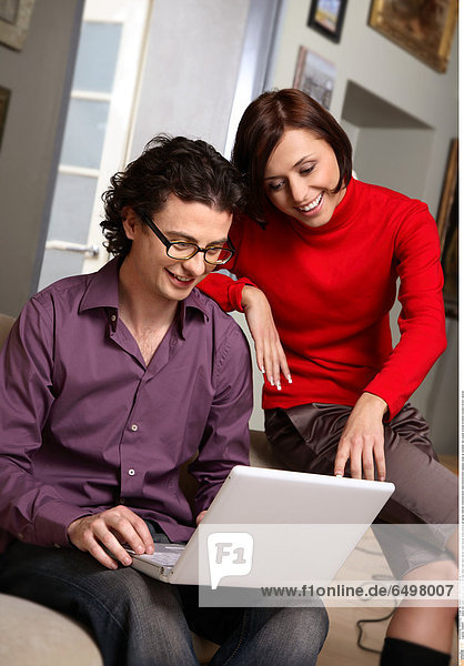 1248597 indoor flat room people young 25-30 rest relax man dark haired violet blouse smile smiling sit laptop internet communication telecommunication glasses close up sweater red couple woman brunette trousers brown vertical