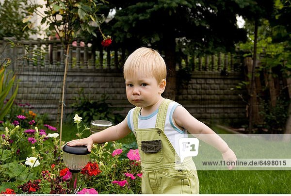 1247031 outdoor day summer people child boy 0-5 fair haired blouse white trousers yellow horizontal garden flower flowers