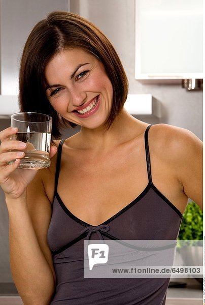 1247196 indoor flat kitchen people woman young 25-30 brunette close up blouse grey hand hold glass water drink diet smile smiling vertical