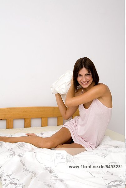 1247051 indoor flat room people woman young girl 20-25 brunette sit bed bedroom white bedclothes rest relax smile smiling vertical foot feet barefoot nightdress pillow