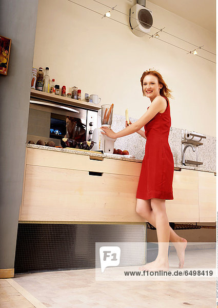 1246494 indoor flat people woman young girl 20-25 blonde fringe stand foot feet barefoot dress red kitchen cupboard kitchen cupboards close up kitchen hand hands smile smiling juice extractor carrot carrots vertical