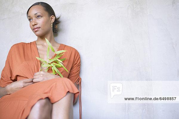 Woman sitting holding leaf