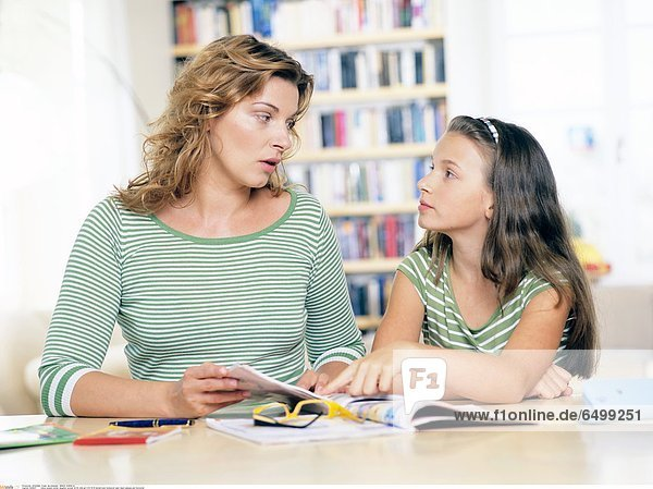 1249037 indoor people mother daughter woman 30-35 child girl 5-10 10-15 blonde book homework learn teach glasses pen horizontal