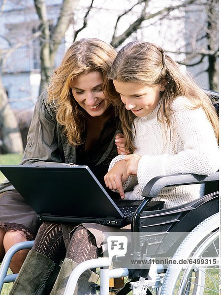 1249074 outdoor people mother daughter woman 30-35 child girl 5-10 10-15 blonde smile smiling laptop notebook personal internet communication compter veeling chair disablement disability physically handicapped vertical