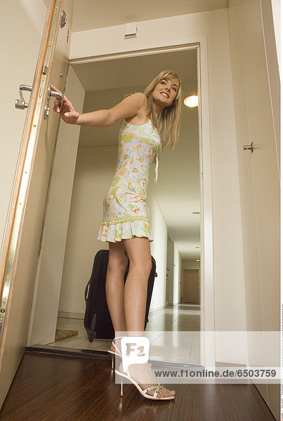 G6GK6449 people one woman girl 20-25 adult blonde fringe smile smiling dress shoe shoes heel heels stand leg lay put wheel suitcase handle hold exit leave indoor day flat hall hallway door vertical