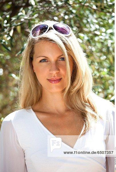 Junge Frau in weißem Oberteil mit Sonnenbrille im Haar