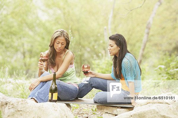 Zwei junge Frauen halten Gläser Wein