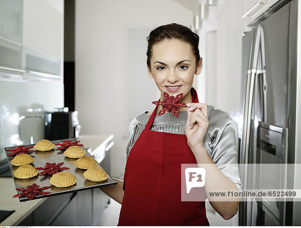 Young woman in red apron while cooking