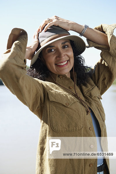 Hispanic woman smiling with hands on head outdoors