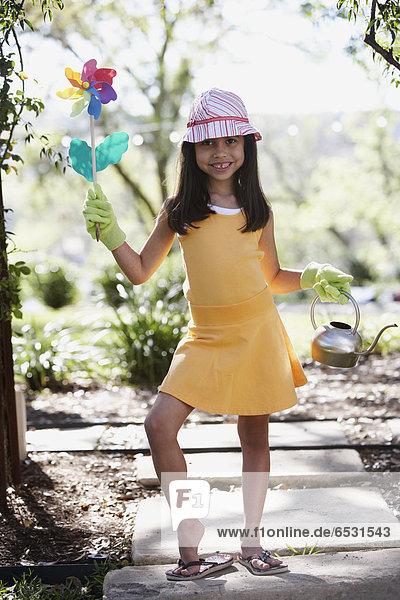 Hispanic girl holding flower pinwheel and watering can outdoors