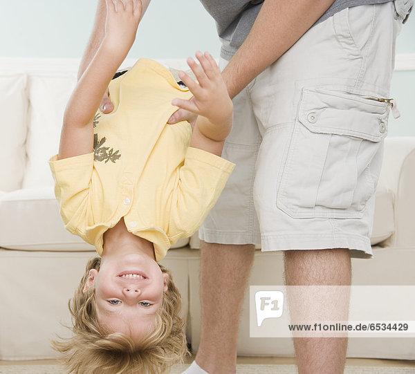Menschlicher Vater  Sohn  halten  jung  kopfüber