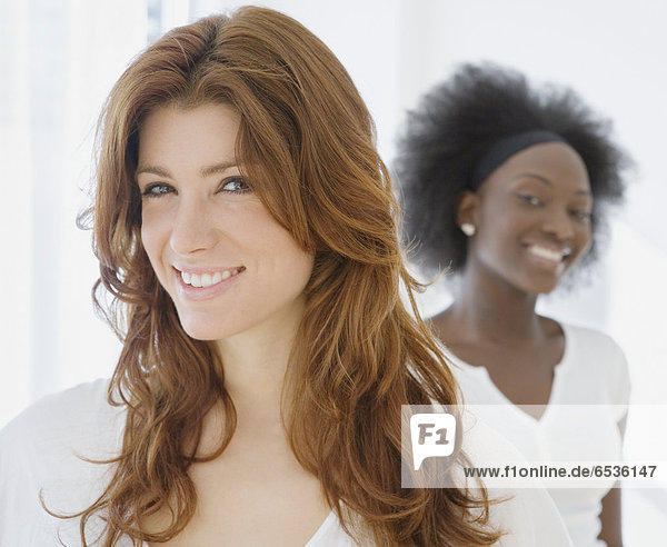 Woman smiling with African friend in background