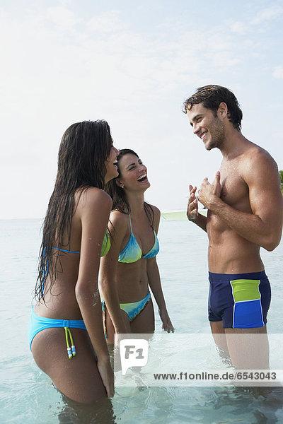 Two women talking to man in water
