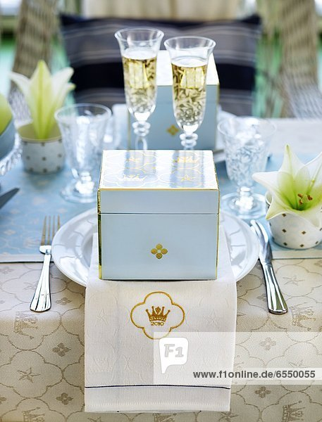 Gift on plate  champagne flutes on background