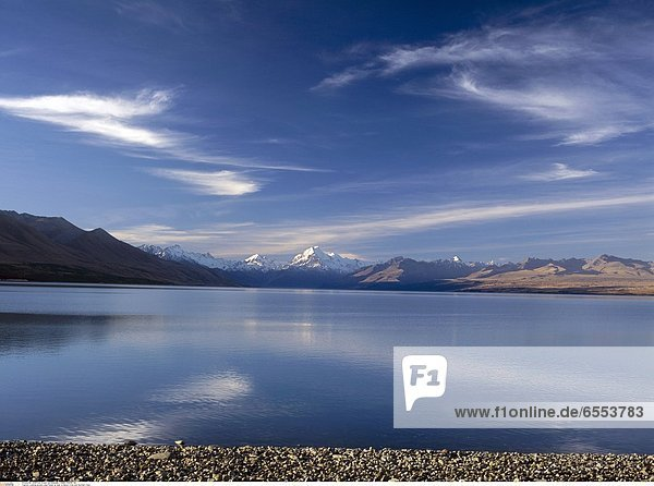 Snowcapped mountains reflected in Lake Wakatipu with clear water and pebbles