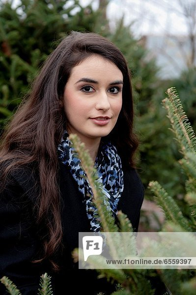 Portrait of a 21 year old brunette woman shoopping in a plant nursery