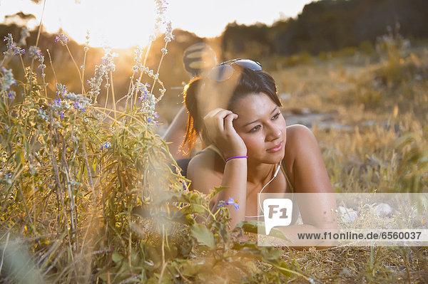 USA  Texas  Concan  Teenagermädchen auf der Wiese liegend mit Kopfhörern