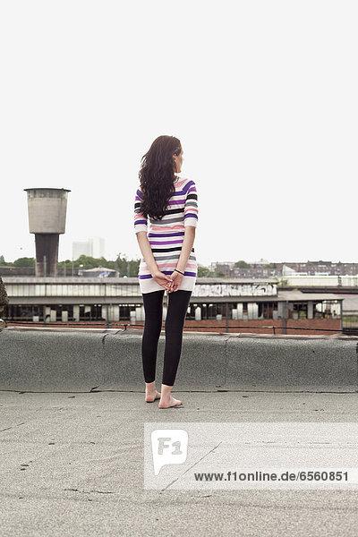 Junge Frau auf dem Dach stehend