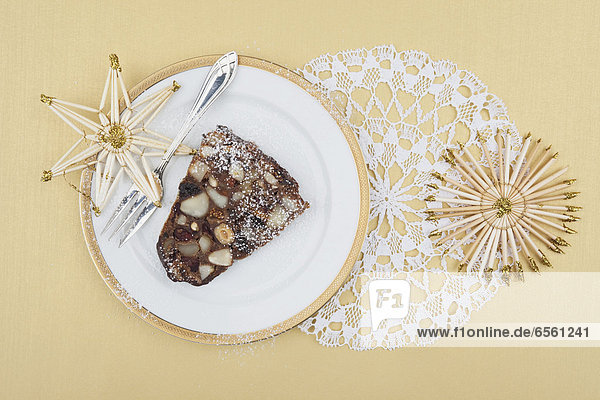 Plate of Christmas fruit cake slice with straw star