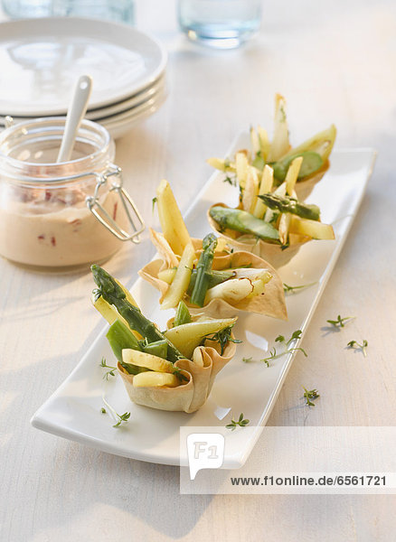 Baked basket stuffed with asparagus and potato salad with chili tomato dip