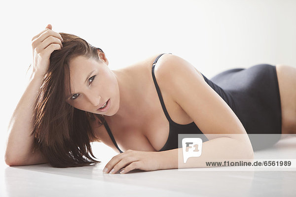 Young woman in black bodysuit  lying on white background