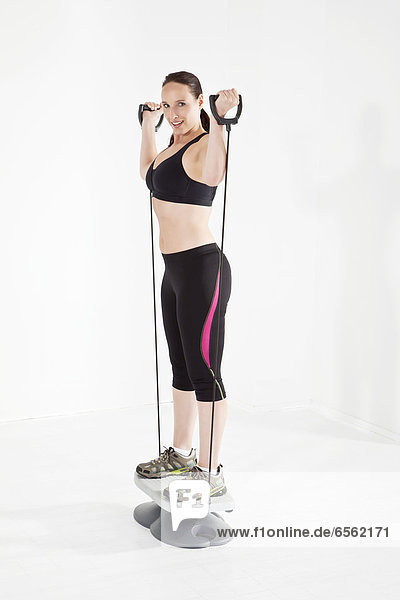 Young woman exercising with resistance band  smiling