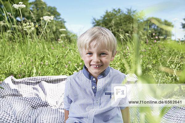 Junge sitzend auf Decke in der Wiese  lächelnd  Porträt