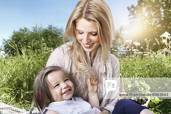 Germany  Cologne  Mother and daughter sitting on meadow  smiling