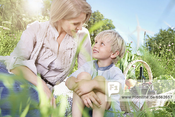 Germany  Cologne  Mother and son sitting on blanket at picnic  smiling