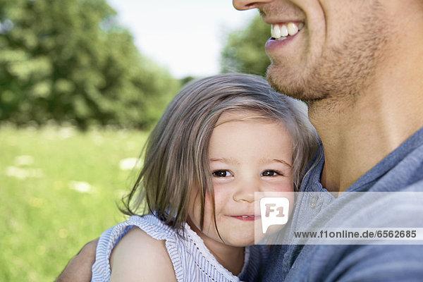 Deutschland  Köln  Vater und Tochter lächeln  Nahaufnahme