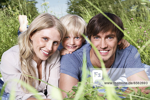 Germany  Cologne  Family lying in meadow  smiling  portrait
