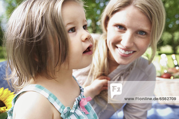 Germany  Cologne  Mother and daughter at picnic  smiling