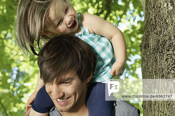 Germany  Cologne  Father carrying daughter on shoulders