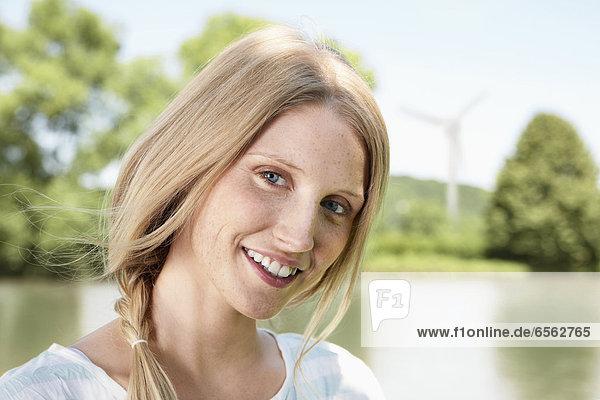 Junge Frau lächelnd  Portrait  Windkraftanlage im Hintergrund