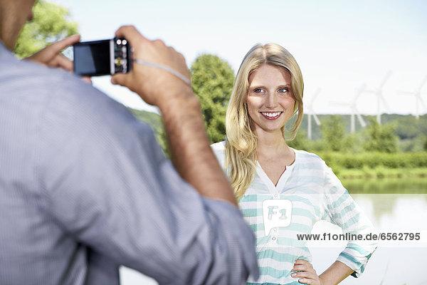 Junger Mann fotografiert Frau