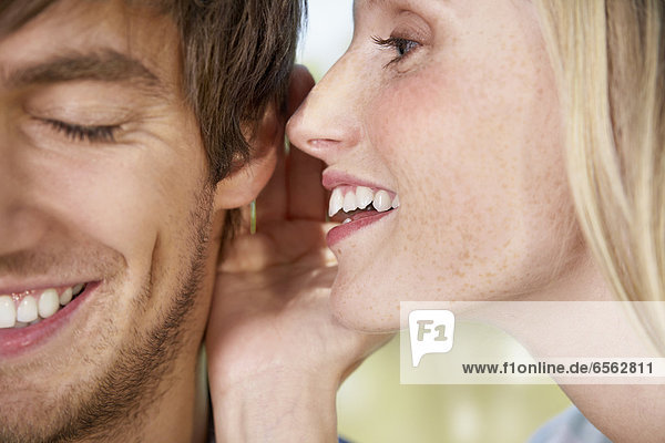 Young woman whispering to man  close up