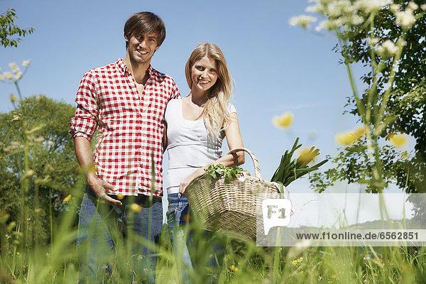 Deutschland  Köln  Junges Paar mit Picknickkorb auf der Wiese  lächelnd  Portrait