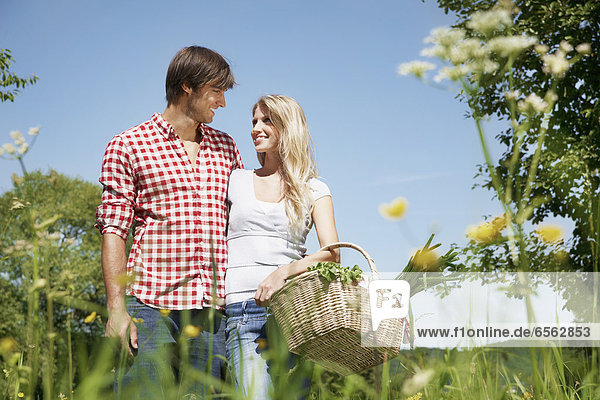 Germany  Cologne  Young couple with picnic basket in meadow  smiling