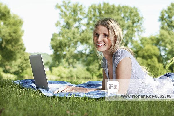 Junge Frau mit Laptop auf der Wiese  lächelnd  Portrait