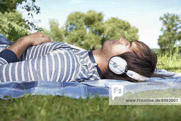 Junger Mann hört Musik auf der Wiese