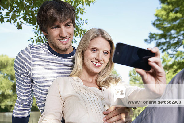 Germany  Cologne  Young couple taking self photograph  smiling
