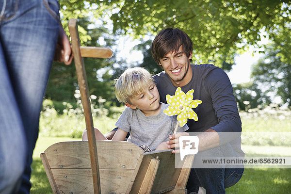 Germany  Cologne  Father and son with paper windmill  smiling