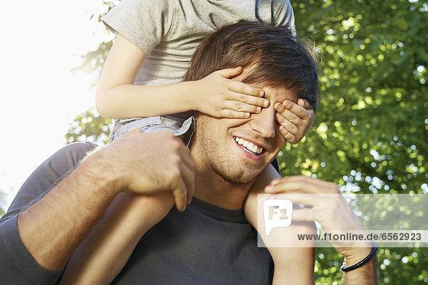 Deutschland  Köln  Vater trägt den Sohn auf den Schultern  bedeckt seine Augen
