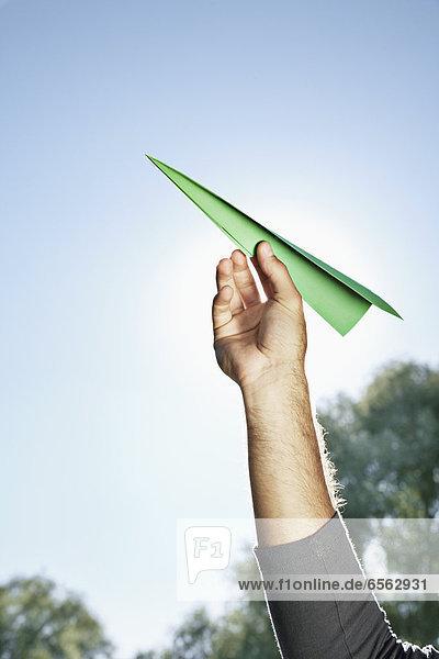 Junger Mann hält Papierflugzeug gegen den Himmel
